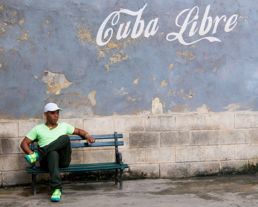 Street Scenes - Man Sitting with Cuba Libre Sign in Havana, Cuba - Copyright 2013 Ralph Velasco