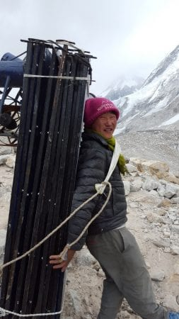 Young man bringing steel cables to Base Camp in Nepal
