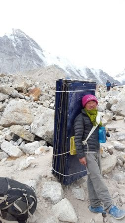 Young Nepali man hiking steel cables into base camp